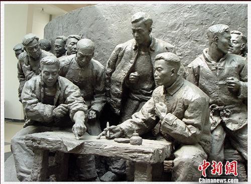 大包干纪念馆内,1978年18位村民按下手印的雕塑。 供图