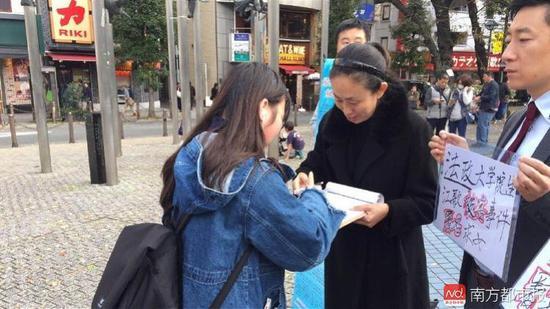 11月11日,江秋莲在东京街头征集签名。
