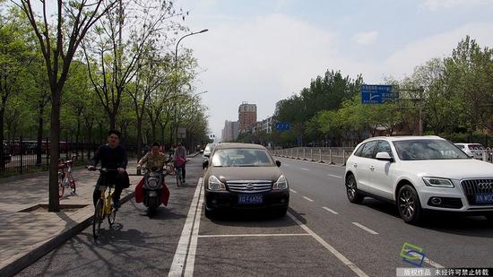 2017年4月14日,北京市石景山苹果园南路出现了一种新式路侧停车位,位置从紧贴便道旁边挪到了机动车道和非机动车道中间。这样的停车位在全市还属首创,目的是为了解决停车难的同时保障非机动车的路权(图片来源:tuku.qianlong.com)。杜建坡摄 千龙网发