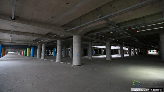 由中国建筑第八工程局承建的北京新机场综合交通中心(停车楼及综合服务楼)项目,地下1层东西贯通,地上3层分为东西两个停车楼,共设成为5345个,其中充电桩车位600个,其布局呼应主航站楼分区运行的功能流程,东西两个独立停车单元分别服务东西侧航站楼旅客(2月23日摄 图片来源:tuku.qianlong.com)。千龙网记者 陈健男摄