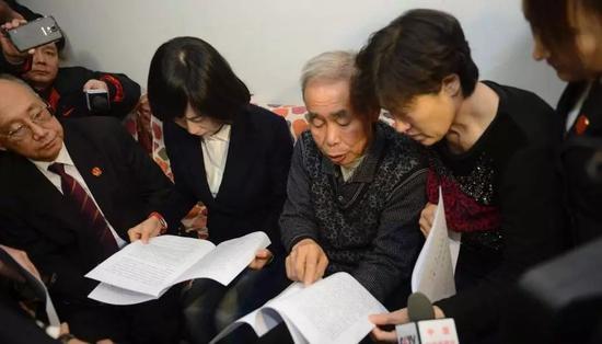 内蒙古高院工作人员上门为呼格吉勒图父母送达再审判决书,判定呼格吉勒图无罪,并送上3万元慰问金。