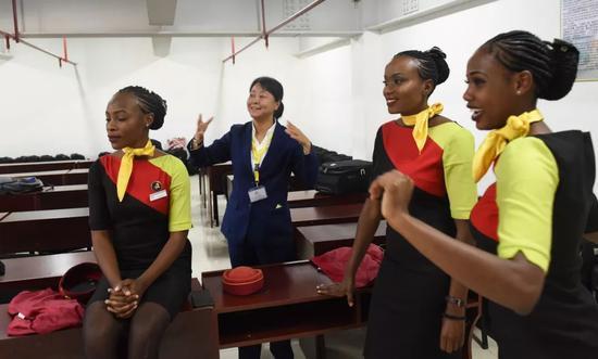 2月2日,在肯尼亚首都内罗毕的蒙内铁路内罗毕南站,中国路桥蒙内铁路运营公司客运车队长黄晓莉(左二)指导肯尼亚女乘务员表演。新华社记者李百顺 摄
