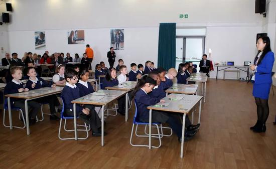 """来自上海的教师为伦敦一所小学学生讲授""""九九乘法表""""的用法。新华社记者韩岩 摄"""