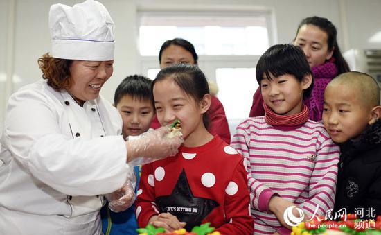 图为小朋友们在品尝村民李会青制作好的花糕。