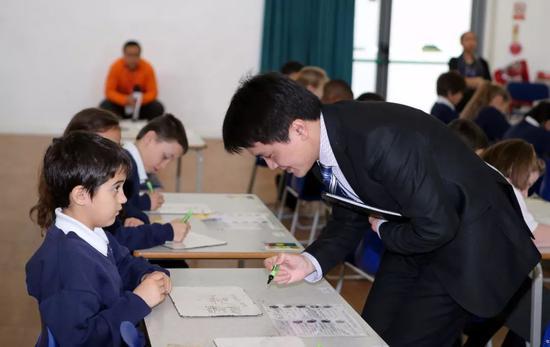 中国数学教师为伦敦一所小学学生批改课堂练习题。新华社记者韩岩 摄