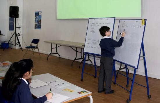英国小学生正在学习利用竖式解题。新华社记者韩岩 摄