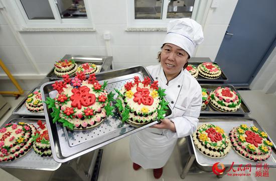 图为村民李会青在展示制作好的花糕。