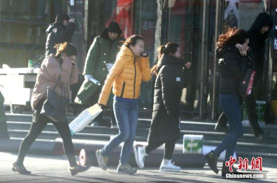 资料图:北京大风降温,市民迎风出行。中新社记者 张宇 摄