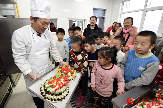 图为邵府村村民向孩子们展示刚出锅的花糕。