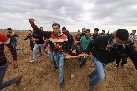 12月7日,在加沙地带南部的汗尤尼斯,巴勒斯坦人救护在与以色列军队的冲突中受伤的人员。新华社发