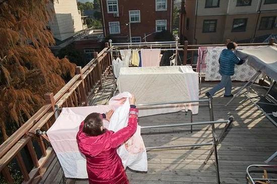 昨天下午2点多,许阿姨和金阿姨在三楼露台收被子。