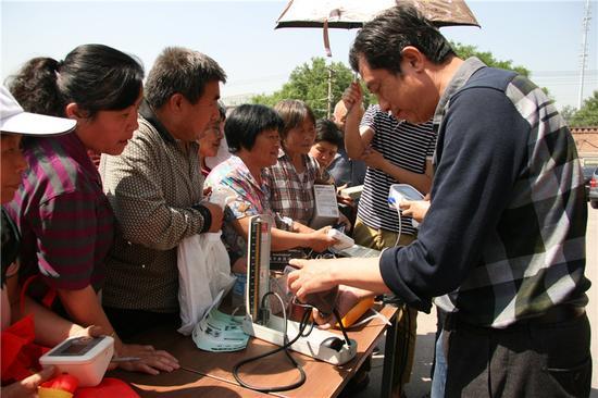 邀请专业医护人员现场为村民检测血压计