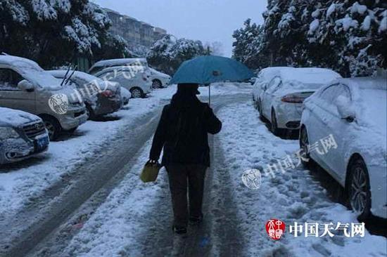 今天早晨,南京某小区市民冒雪出门,路上已经满是积雪。