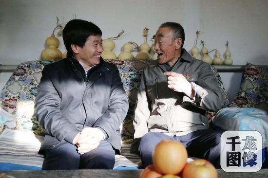 """1月19日,2018年""""三下乡""""活动正式启幕。图为北京市委常委、宣传部长杜飞进(左)以及市""""三下乡""""成员单位领导带着春节礼包,走到村民家中送上新年祝福。杨连荣摄 千龙网发"""