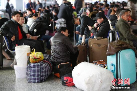 资料图:在铁路上海站售票大厅内,旅客们背上行李回家。 殷立勤 摄