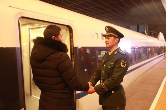 图说:中队长徐剑勇(右)送王隆宇上火车。王志鹏 摄