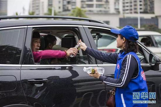 △ 2月24日,在海南省海口市滨海大道,一名志愿者为滞留旅客提供饮用水