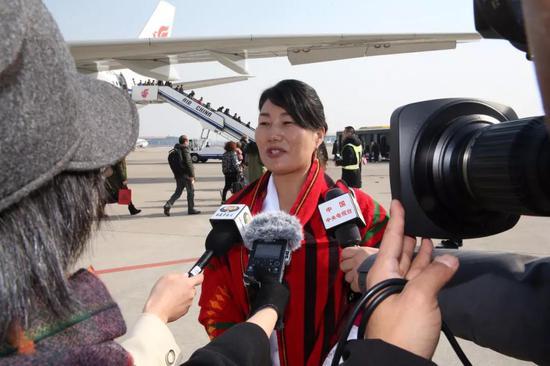 """代表们一抵达北京,就被等候在机场的记者团团""""包围""""。记者 姚海全 摄"""