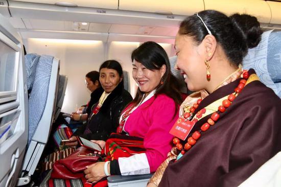 代表们在飞机上交流。 记者 姚海全 摄