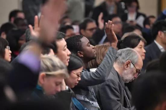 ▲在记者会现场,中外记者纷纷举手提问。(新华社)