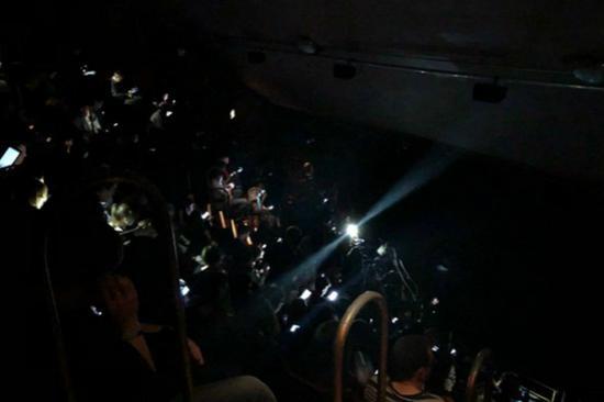 戏剧院里观看演出的民众用手机灯光照亮场内。(图片来源:英国《每日邮报》)