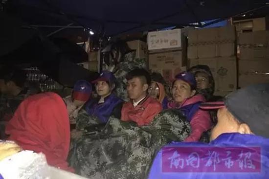 23日凌晨,风雨寒冷中,志愿者盖着大衣,依偎在一起取暖。即便如此,他们依然坚守岗位。 南国都市报 图