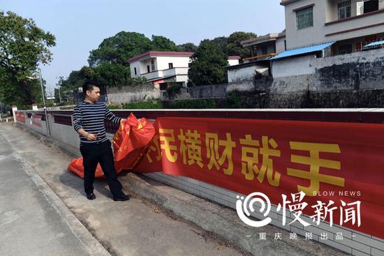 """关塘村工作人员在清理汽车经销商""""祝贺村民横财就手""""的条幅"""
