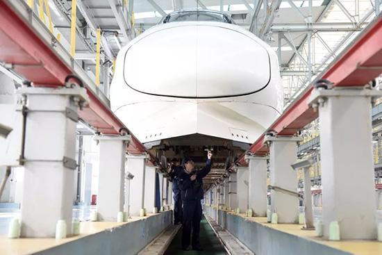 3月11日,张佩和同事们正在检查动车组件。
