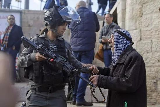 12月7日,在耶路撒冷老城,一名以色列安全人员在大马士革门外驱逐巴勒斯坦抗议者。新华社/法新