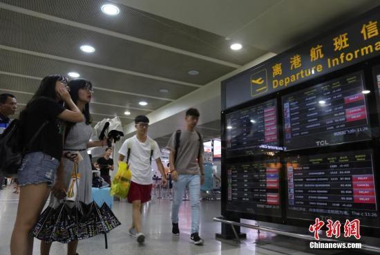 资料图:乘客查看航班信息。 中新社记者 尹海明 摄