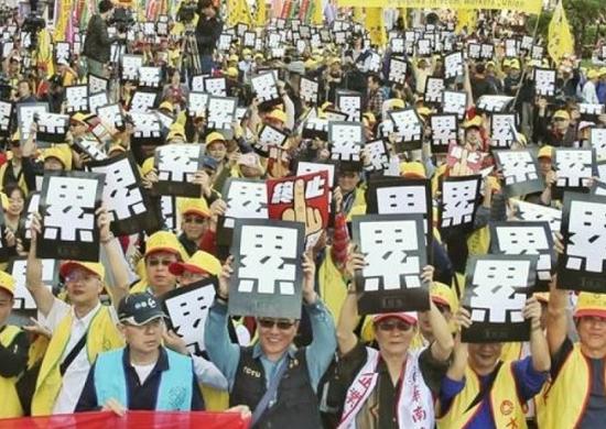 """不少台湾网民认为,台湾最便宜的用品是""""人力""""。图为劳工团体去年12月的游行,高举标语""""累""""。(资料图片)"""