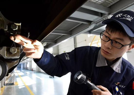 3月11日,张佩正在检查动车组件。