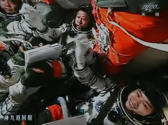 手控对接成功,三人(中间为刘旺)在返回舱握手欢呼。(秦宪安 摄)