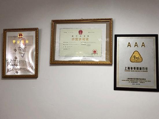 """泰申国际旅行社办公室进门显眼处挂着公司的营业执照、经营许可证和""""AAA上海市登记旅行社""""证书"""