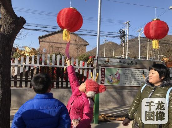 """19日上午,北京市2018年文化科技卫生""""三下乡""""集中示范活动,来到昌平区南口镇花塔村,为农民群众带来文艺演出、健康义诊等。图为村民猜灯谜。千龙网记者 秦胜南摄"""