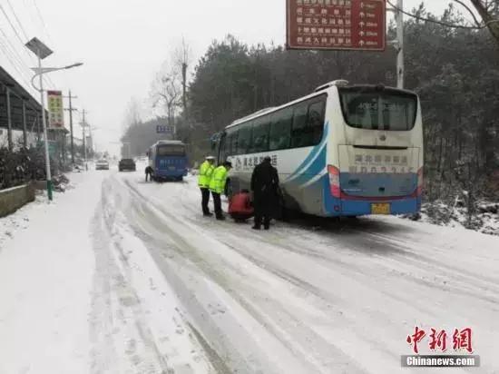 """资料图:湖北宜昌遇强降雪,路政交警""""保畅总动员""""。 李开明 摄"""