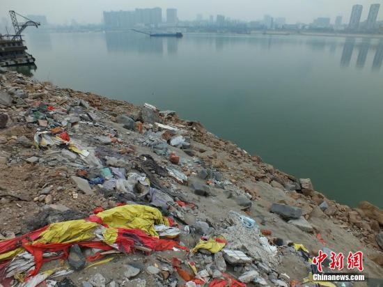 资料图:长江河道边堆积渣土垃圾成山。