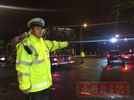 23日凌晨,执勤交警黄清顶着寒风冷雨,在路口指挥交通。南国都市报 图
