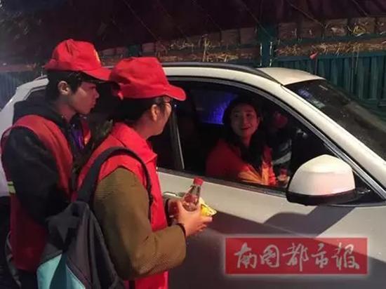 23日凌晨,志愿者看见一女士晕车呕吐,随即送上水、饼干和问候。南国都市报 图