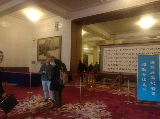 外国记者在二楼大厅入口处领取会议文件。