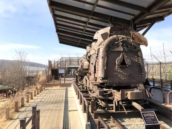 一座在朝鲜半岛非武装地带废弃半个世纪的蒸汽火车车头,静静躺在铁丝网筑成的围墙旁,千疮百孔的车身上满是弹痕。