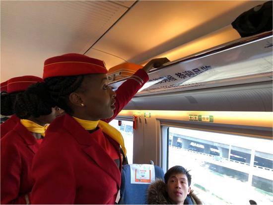 2018年2月8日,肯尼亚女乘务员在中国动车上主动整理旅客行李。(中国路桥供图)