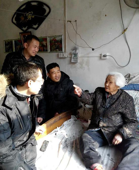 何陆翼(左一)在村民家中走访