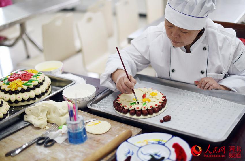 图为河北枣强县邵府村村民李会青正在制作花糕。