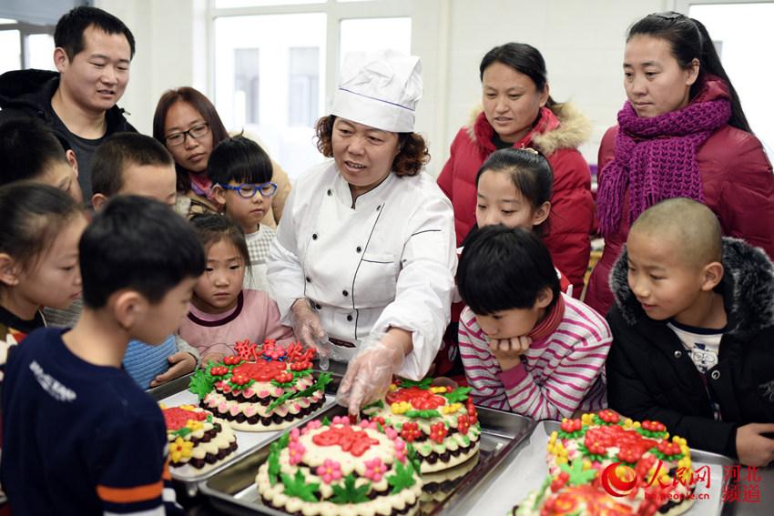 图为村民李会青为村民讲解蒸花糕的传统习俗。