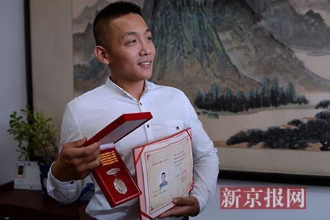 6月18日,一脚将持刀男子踹倒的健身房搏击教练周凡凡向记者展示刚刚获得的《北京市见义勇为人员证书》。