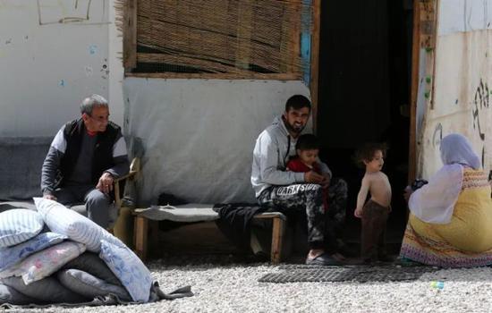 4月12日,在希腊雅典以北约86公里处的里措纳难民营,一对夫妇照顾孩子。新华社发