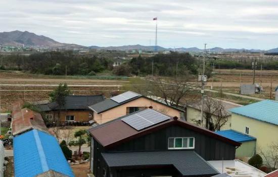 这是4月24日拍摄的韩国大成洞村一角,远处的朝鲜国旗清晰可见。 新华社记者李鹏摄