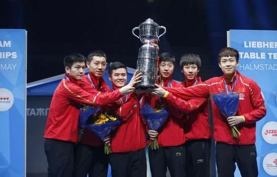 图为中国队队员和教练刘国正(左三)捧起斯韦思林杯。