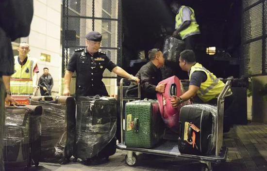 马来西亚警方将多个箱子装车。